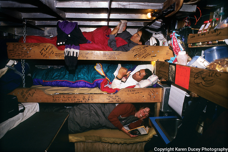 "The F/V Little Comfort from top to bottom: Kevin Imai, ken Larson and Karen Ducey sleep in their bunks, or racks, during the Bristol bay sockeye salmon fishery in July 1994.  Bristol Bay is home to the world's largest sockeye salmon fishery.  The commercial salmon drift gillnet fishing fleet is limited to boats no longer than 32 feet in length.  There were over 1,800 permanent entry permits listed in 2002 which each vessel is required to have.  Typically boats fish with two or three deckhands.  Peak of the season is around July 4th in this fishery which lasts about a month. The rivers also get a fair amount of chum, king, and chinook salmon. Bristol Bay is located in the southwest part of Alaska. This fishery is managed by ""the Alaska Department of Fish and Game"" and is a sustainable fishery.  Until around the year 2000, fishing on the Egegik North Line was lively and lucrative.."