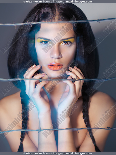 Artistic expressive beauty portrait of a young beautiful woman behind barbed wire