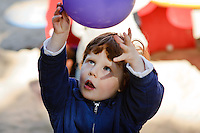 Young boy playing with a purple balloon.