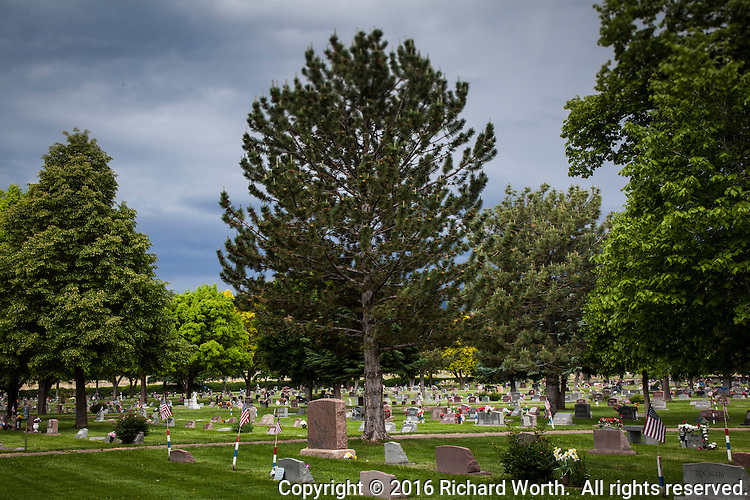 In a cemetery, in a small Colorado town, trees stand over granite markers, some with flowers and some with flags honoring military veterans  on the Friday before Memorial Day.