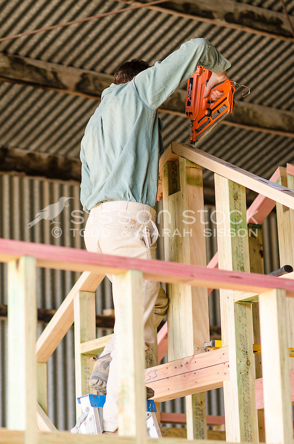 Builder (young adult male) using nail gun on a wooden frame at a construction site, undercover,Queenstown, South Island, New Zealand - stock photo, canvas, fine art print