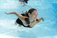 A young woman in evening dress floats underwater Model release available