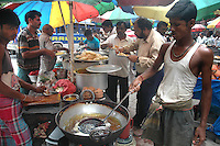 Food are being prepaired at a street food stall while office workers having lunch during break  in Dalhousie area of Kolkata. Street food stalls are serving the office goers for decades. All kind of Indian foods are available on the street at an affordable price. They sale them openly. Street food stalls are another results of unempoloyment and over poppulation. They serve millions of people in India. Kolkata, West Bengal,  India  7/18/2007.  Arindam Mukherjee/Landov
