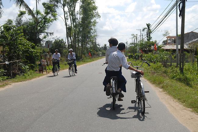 School children ride  their bikes home from school in Hoi An, Vietnam.