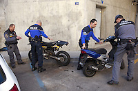 Switzerland. Geneva. Paquis neighborhood. Two police officers and two traffic policemen control the  identities of two stolen motor vehicles, a motorbike and a scooter. Both police officers are wearing a ballistic vest, bulletproof vest or bullet-resistant vest which is an item of personal armor that helps absorb the impact from knives, firearm-fired projectiles and shrapnel from explosions, and is worn on the torso. Soft vests are made from many layers of woven or laminated fibers and can be capable of protecting the wearer from small-caliber handgun and shotgun projectiles. 16.03.12 &copy; 2012 Didier Ruef..
