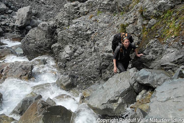 Jente på vei opp et bratt bekkeløp. Harman Pass, New Zealand. ---- Girl on the way up steep, rocky stream, Harman Pass, New Zealand.