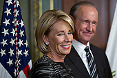 Betsy DeVos, United States Secretary of Education, stands with her husband Dick DeVos Jr., right, before being sworn in by U.S. Vice President Mike Pence in the Vice President's Ceremonial Office in Washington, D.C., U.S., on Tuesday, Feb. 7, 2017. DeVos squeaked through a history-making Senate confirmation vote to become U.S. education secretary, as Vice President Mike Pence broke a 50-50 tie and Republicans staved off last-minute defections that would have killed her nomination. <br /> Credit: Andrew Harrer / Pool via CNP