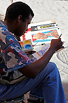 Central America, Cuba, Havana. A street artist paints a scene in old Havana.