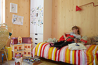 The artist Richard Woods has built a timber house where he can both create and showcase his bold, bright work.  Woods shares with his wife Jess Spanyol, a children's book author, and their three children. 10-year-old Augusta in her bedroom