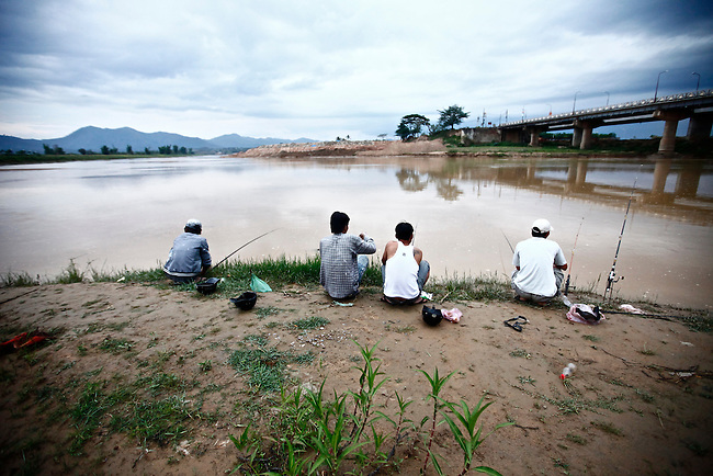 Men fish in the Dakbla River at dusk in the Central Highlands town of Kon Tum, Vietnam. April 13, 2012.