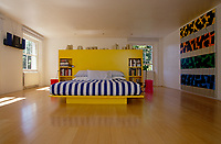 In the bedroom of a house designed by Richard Rogers a double bed with an integral headboard in bright yellow lacquer creates a cheeful focal point to the space