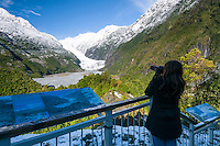 Female tourist photographing Franz Josef Glacier in winter, Westland National Park, West Coast, World Heritage Area, South Westland, New Zealand