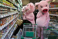 Moscow, Russia, 03/03/2011..A shopper reaches for produce as members of health campaign group Pigs Against check the sell-by dates and quality of food in a city centre supermarket while dressed in pig costumes.