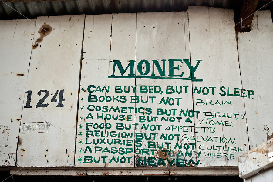 Arusha, Tanzania 2010 - Some words of wisdom about money painted on the wall above a vendor's stall in the crafts market in downtown Arusha.