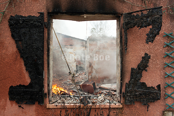 total loss burned out house with still smoldering remains