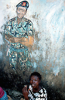 Sierra Leone. Freetown. Memory of the 10 years war. Drawing on the wall in the town center of a soldier's face. A woman seated on the ground smokes a cigarette. © 2002 Didier Ruef