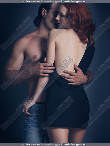Artistic soft sensual portrait of a young sexy couple. Man with bare torso embracing a woman in dress with open low back.