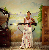 Nadia, a 14 year old Roma girl, stands in her bedroom holding a loaded shotgun. The gun hangs on the wall of her room, in the new home that the family built. Two weeks after this photo was taken Nadia would be getting married. IN the roma camp of Sintesti..