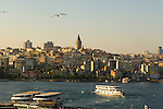 A ferry boat on the Golden Horn passes beneath the Galata Tower in Istanbul, Turkey