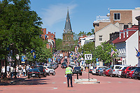 A traffic control officer directs traffic on busy Main street with the spire of St. Anne's Episcopal Church in the distance in Annapolis, Maryland.