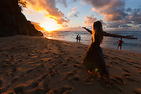 Sun sets on Kauai's north shore as people enjoy the last rays of light. Some yoga to end the day seems right.