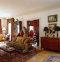 A velvet olive beige sofa sits in the centre of this living room with large Persian rugs