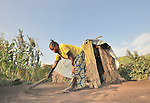 Bosco Mosengo sweeps the dirt around her hut in a displaced persons camp in the village of Kirotshe, about 40 km west of Goma. A quarter of a million people have been newly displaced by fighting in the eastern Congo, where some 5.4 million have died since 1998 from war-related violence, hunger and disease.