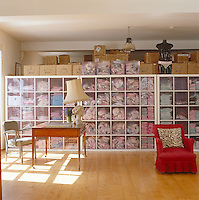The wall-to-wall storage unit comprises numerous transparent drawers containing Pom Lampson's range of lingerie