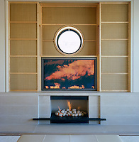Japanese-style shoji panels made from silk slide open to reveal a television located above the contemporary fireplace
