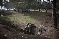 In this Sunday, Dec. 16, 2012 photo, a lifeless body of a Syrian army soldier remains laying beside a trench after it was died during heavy clashes inside one militar academy besieged by rebels at the north of Aleppo, Syria. The Free Syrian Army took control over the Academy after several hours battling the troops loyal to President Bashar al-Assad. Among the casualities are one FSA General and one Syrian journalist. (AP Photo/Narciso Contreras)