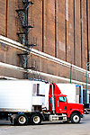 Several refrigerated trailers are lined up at the dock door of a warehouse in the meat packing district of Chicago.