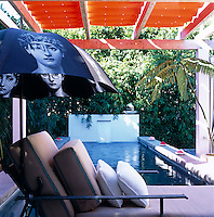 A wrought-iron sun lounger in the shade of a Fornisetti parasol with the long narrow swimming pool beyond