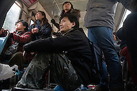 Volunteer animal workers ride a bus back to Nanjing after a visit to Ha Wenjin's no-kill dog and cat rescue farm outside Nanjing, Jiangsu, China.