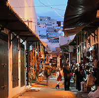 A shopping street selling leather goods in a souq or market in the medina or old town of Tetouan, on the slopes of Jbel Dersa in the Rif Mountains of Northern Morocco. Tetouan was of particular importance in the Islamic period from the 8th century, when it served as the main point of contact between Morocco and Andalusia. After the Reconquest, the town was rebuilt by Andalusian refugees who had been expelled by the Spanish. The medina of Tetouan dates to the 16th century and was declared a UNESCO World Heritage Site in 1997. Picture by Manuel Cohen