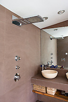 Mounted on the elegant stone walls of the bathroom a large shower is equipped with varying heads in a single fixture
