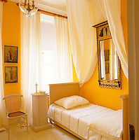 The guest bedroom of an apartment in St Petersburg has been painted a warm and welcoming sunflower yellow