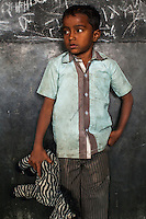 Aman, 6, poses for a portrait with a soft toy in the Guria Non-Formal Education center in the middle of the Shivdaspur red light district, Varanasi, Uttar Pradesh, India on 20 November 2013. Guria uses the soft toys as a form of therapy for the children of the women in prostitution and also use it as signals of the children's emotional wellbeing.