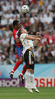 JUNE 9, 2006: Munich, Germany: Costa Rican defender Michael Umana (4) goes up for a header against German forward Lukas Podolski (20) during the World Cup Finals in Munich, Germany.  Germany defeated Costa Rica, 4-2.