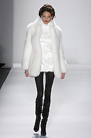 Model walks runway in an ivory saga royal fox mini coat lined w/french lace, and ivory reembroidered french lace mini dress, from the Zang Toi Fall 2012 &quot;Glamour At Gstaad&quot; collection, during Mercedes-Benz Fashion Week New York Fall 2012 at Lincoln Center.