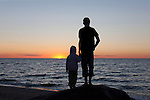 Young Kids Standing, Silhouettes at Sunset on Beach