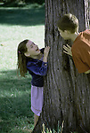 A boy and girl playing peek-a-boo around a tree.