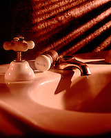 Old fashion sink leaks leaking water waste wasteful warm light shadows on textured wall small drop droplet of water from old fashion ceramic faucet