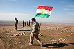 DUZ, IRAQ: A Kurdish peshmerga fighter plants the Kurdish flag on top of a hill in the disputed territories. ..Tensions rise in the disputed territories claimed by both the Central Iraqi Government and the semi-autonomous Kurdish region. Kurdish peshmerga fighters and Iraqi soldiers have both been deployed by their respective governments to the disputed territories...Photo by Kamaran Najm/Metrography