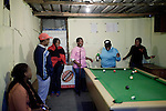 CAPE TOWN, SOUTH AFRICA - OCTOBER 19: Zikona Moloyinyan (c) plays pool with friends in a gay only bar on October 19, 2011 in Khayelitsha outside Cape Town, South Africa. Cape Town is a city known for tolerating gays and lesbians except in the townships where they get harassed and often attacked. Some women have been raped in so called corrective rape, where men rapes them to make them women again. They can't show their love freely on the streets in the townships so they usually have to meet in houses and this bar.  (Photo by Per-Anders Pettersson)