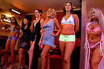 "Sex workers line up for a customer in the parlor of the Moonlite Bunny Ranch brothel in Mound House, NV on Friday, July 28, 2006...The Moonlite Bunny Ranch brothel in Mound House, Nevada - just a few miles from the state capital in Carson City - first opened in 1955. The Ranch is a legal, licensed brothel owned by Dennis Hof. It's featured in the HBO series ""Cathouse."""