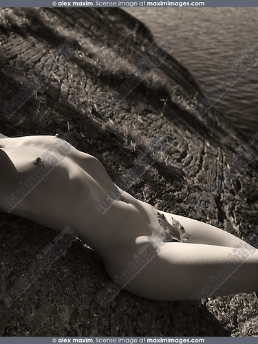 Nude woman lying on a rocky shore by the water in autumn nature scenery