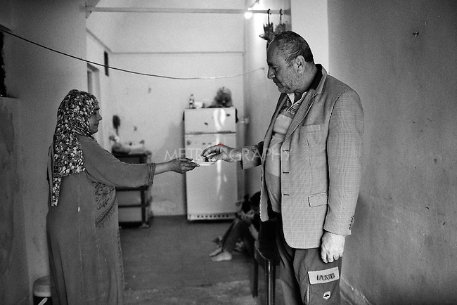 25..3.2015 Kirkuk,Iraq. Ghanim (Christian) is paying a visit to Widad's house and she offers him some sweet which were given to her by the muslim mosque to celebrate the birth of profit Mohammed.