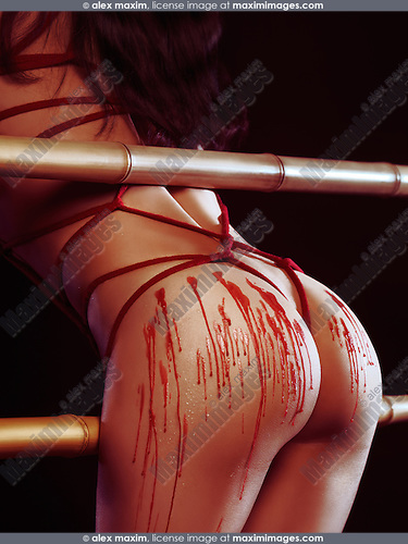 Artistic erotic photo of a sexy woman with red rope japanese bondage shibari and melted wax drips on her buttocks