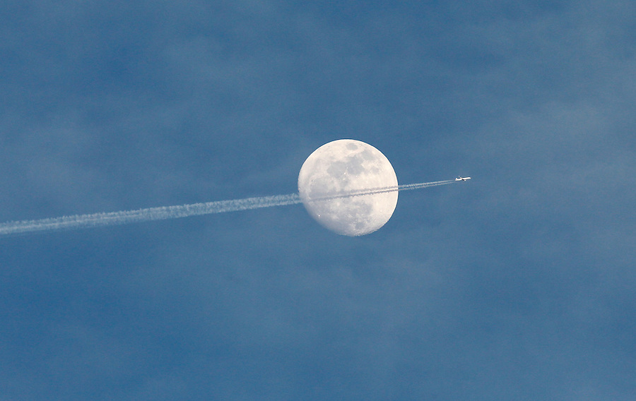 A plane passes by the moon.