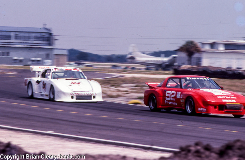 #92 Mazda RX-7 of Terry Visger and Lee Mueller (17th place) and #94 Porsche 935 of Don Whittington and Bill Whittington (12th place) 12 Hours or Sebring, Sebring International Raceway, Sebring, FL, March 19, 1983.  (Photo by Brian Cleary/bcpix.com)